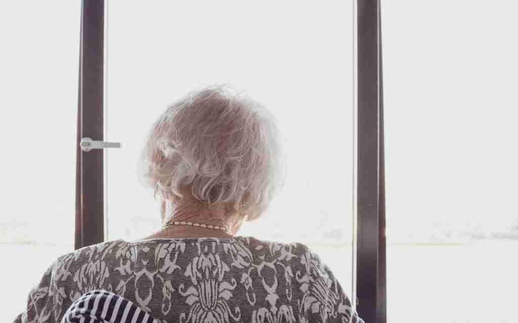 An elderly woman looking out of the window of a senior home