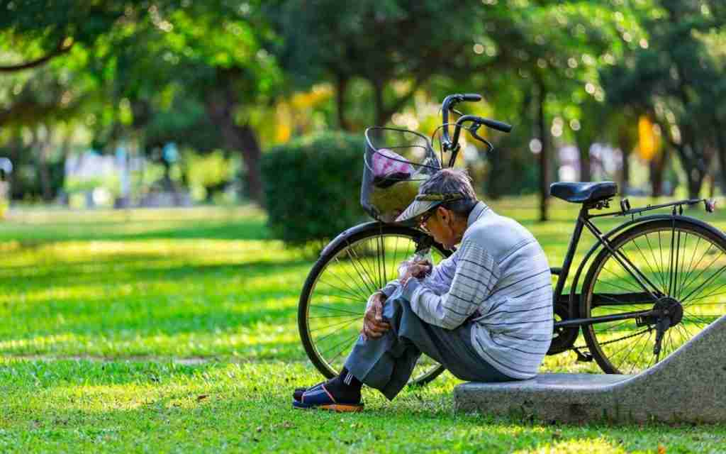 An old man sitting on the ground in a park